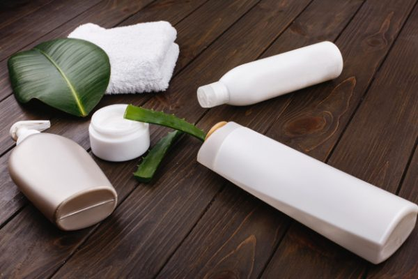 white-towel-bottles-shampoo-conditioner-lie-table-with-green-leaf-aloe_8353-7050
